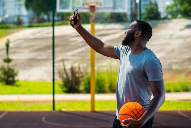 彼の携帯電話でselfieを作るアフロバスケットボール男