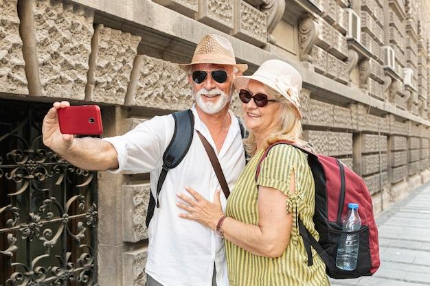 老夫婦の携帯電話でselfieを取る