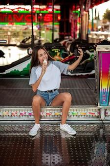 Selfieを取ってアイスクリームを食べる女性