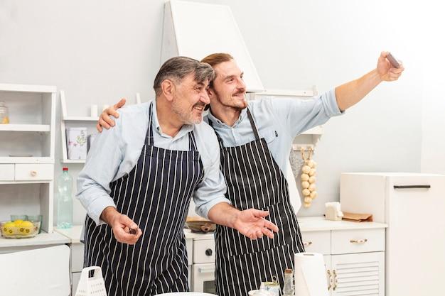 父と息子が台所で、selfieを取って