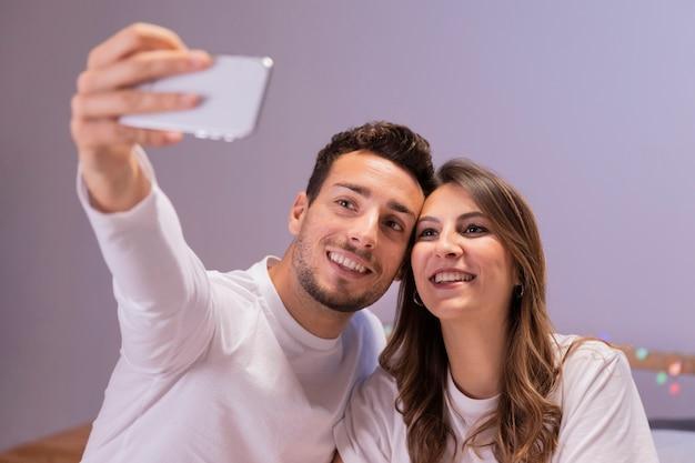 Selfieを取ってベッドで若いカップル