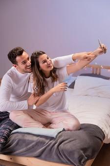Selfieを取ってベッドで幸せなカップル