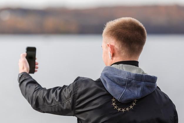 イヤホンで音楽を聴きながら、selfieを取って背面図男