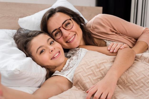 Мать и дочь, принимая selfie вместе в постели