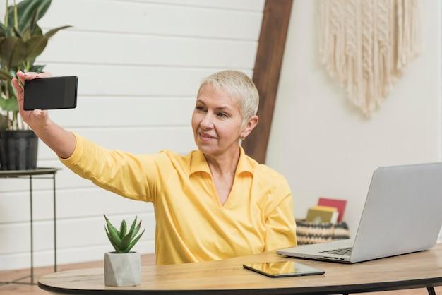 スマイリー年配の女性、selfieを取る