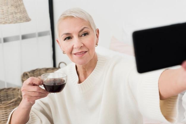 高齢者の女性がコーヒーカップを押しながらselfieを取る