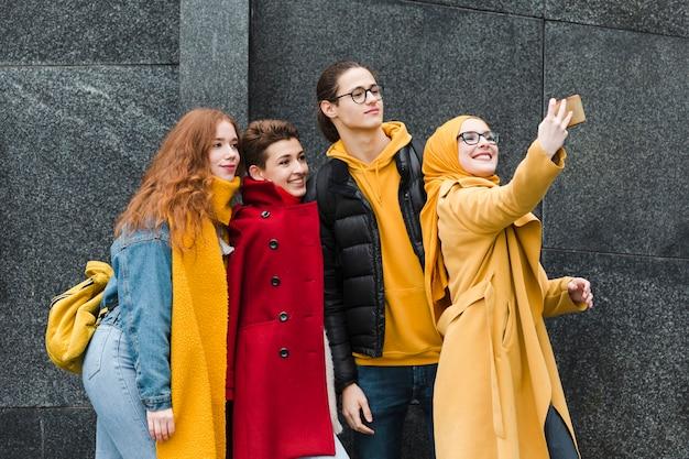 一緒に、selfieを取って幸せなティーンエイジャーのグループ