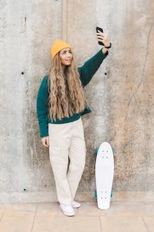 Selfieを取ってスケートボードを持つ女性