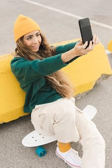 Selfieを取ってスケートボード上の女性