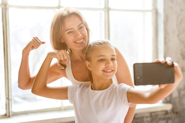 母と娘の腕の筋肉を曲げるselfieを取る