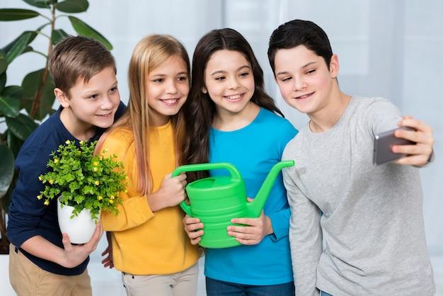 花に水をまきながらselfieを取る子供たちのグループ
