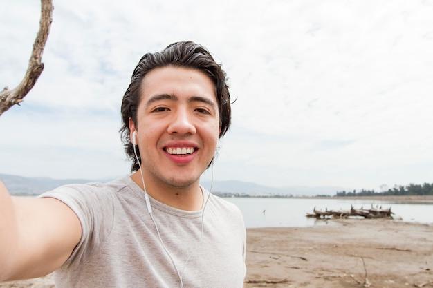 Молодой человек принимает selfie в природе