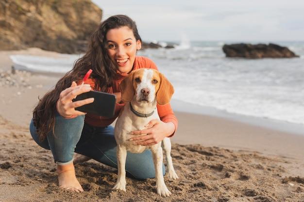 犬と一緒にselfieを取る若い女性