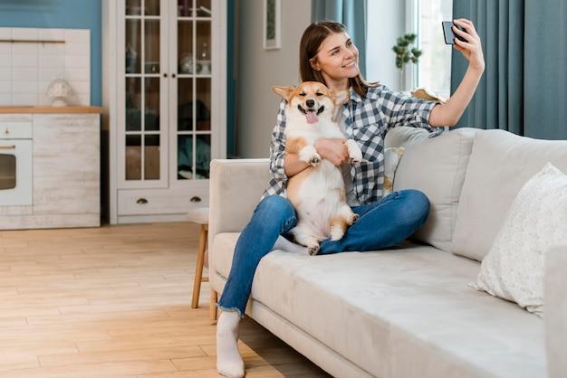 彼女の犬と一緒にselfieを取ってソファの上のスマイリー女性