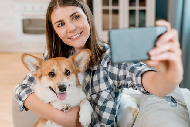 彼女の犬と一緒にselfieを取る女性