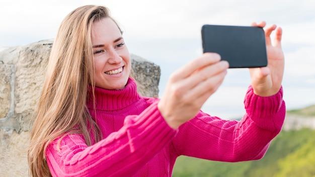 屋外、selfieを取って美しい若い女性