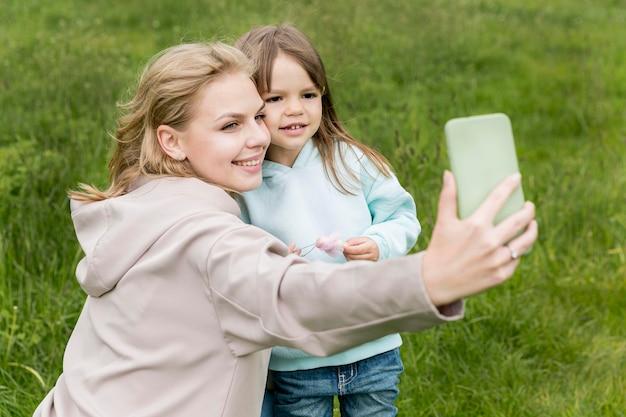 屋外の若者とお母さん、selfieを取る