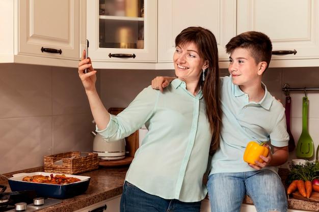 母と息子が野菜と一緒にselfieを取る