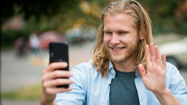 Вид спереди смайлик человек принимает selfie на открытом воздухе