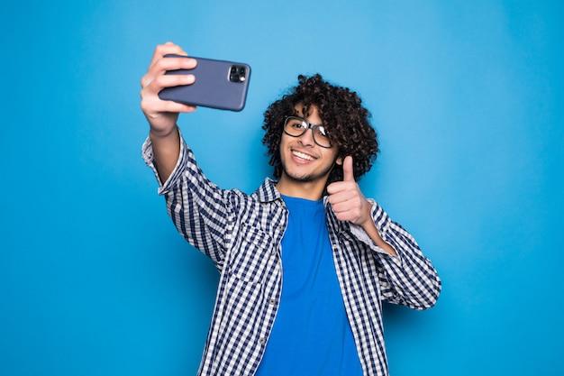 孤立した青い壁に、selfieを作る若い巻き毛のハンサムな男