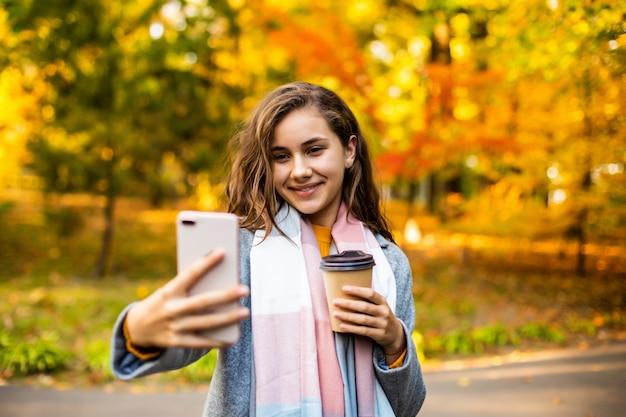 持ち帰り用のコーヒーを保持している、秋に屋外のスマートフォンでselfieを取って幸せな若い女。