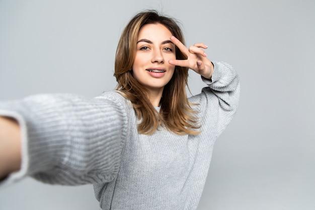 灰色の壁に分離されたスマートフォンでselfieを取っている間平和のジェスチャーを示すかなり陽気なブルネットの女性