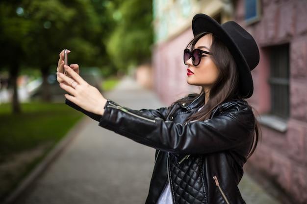 通りで彼女のスマートフォンでselfieを作る魅力的な若いアジアの女の子
