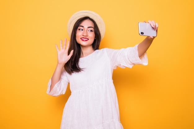 黄色の壁に分離された携帯電話を持つ若いアジア女性selfie