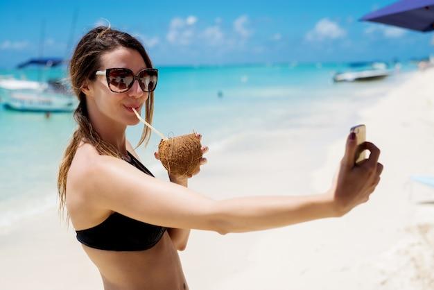 美しい晴れたビーチでピナコラーダカクテルを飲みながら、selfieを作る魅力的な若い女性。