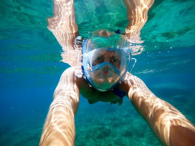 棒でselfieを取っている間夏休みにシュノーケリングマスクが付いている表面の下のターコイズブルーの海で泳いでいる若いダイバー男の水中ビュー。