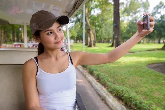 電話でselfieを取る若い美しいアジア観光女性