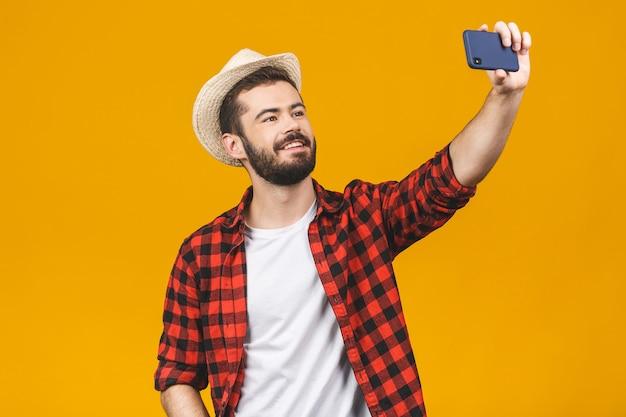 黄色の壁に分離されたスマートフォンで帽子を取ってselfieの陽気な若い旅行男。