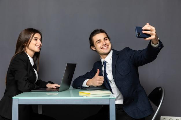若いビジネス同僚のカップルがテーブルの上に座って携帯電話でselfieを取る