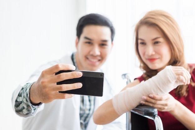 女性患者と笑みを浮かべて男性医師のselfieは、より良い癒しのためにアームスプリントを着用します。