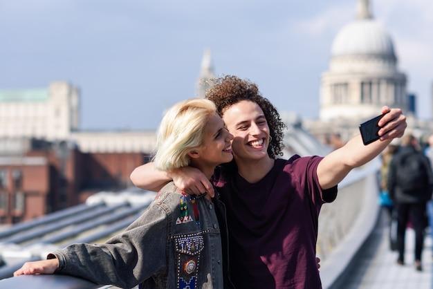 ロンドンのミレニアムブリッジでselfie写真を撮る幸せなカップル