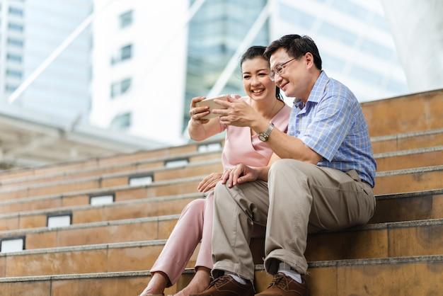 市内の階段に座ってスマートフォンと一緒に幸せなアジアカップルシニア観光客selfie写真