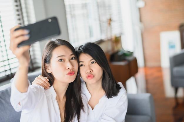 リビングルームでスマートフォンselfieを使用して幸せなアジアのガールフレンド