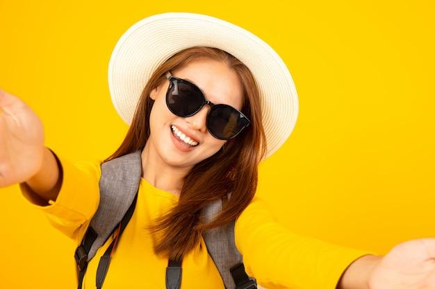 Азиатская женщина наслаждаясь selfie с собой изолировала на желтой предпосылке.