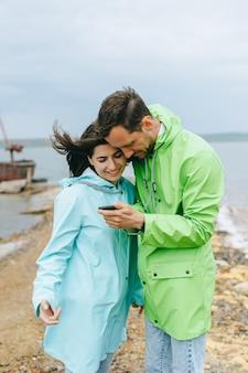 色付きのレインコートで美しいカップルは海の近くにselfieを作る