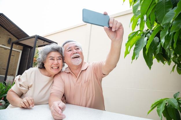 携帯電話でビデオ通話チャットで話している、またはselfie、高齢者とオンライン活動のためのスマートテクノロジーを取る接続された概念を維持するアジアシニアカップル