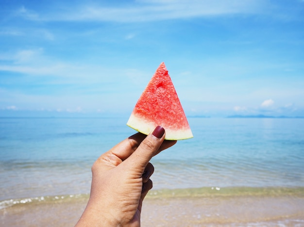 夏のビーチの背景にスイカを持っているselfie手。