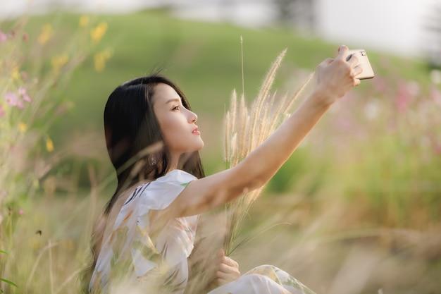 ライフスタイルの肖像画公園の花でスマートフォンにselfieを座っている美しいアジアの女性の女の子