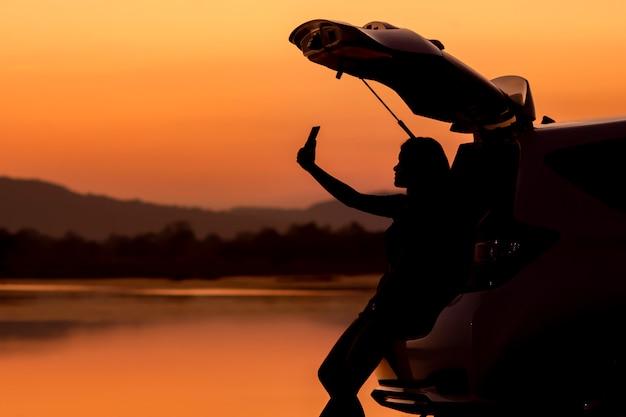 日没の観光スポットでselfieを取っているシルエットアジアの女の子。