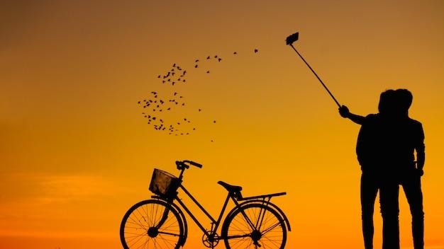 夕焼け空にスマートフォンでselfieを取る男性と女性のシルエット:シルエット写真。