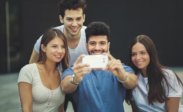 一緒にselfie写真を撮る友人のグループ
