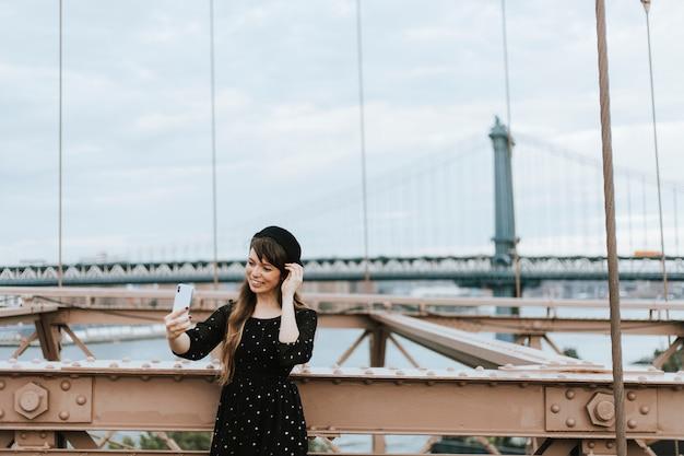 米国ブルックリン橋の上、selfieを取っている女性