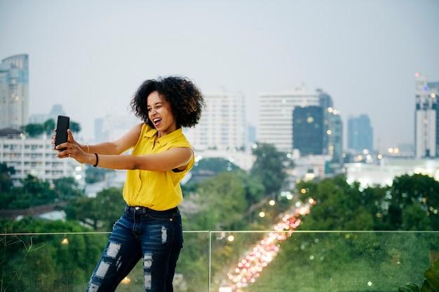 都市の景観でかわいいselfieを取っている若い女性
