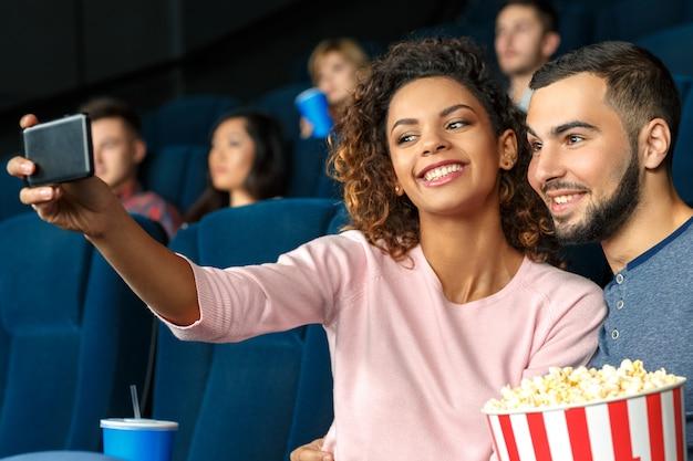 セルフィーを撮ってください。地元の映画館で時間を過ごしながらスマートフォンを使用してselfieを一緒に取っているかわいい若いカップルの水平ショット