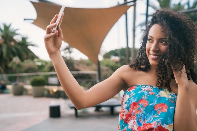 電話でselfieを取るアフロアメリカンのラテン女性。