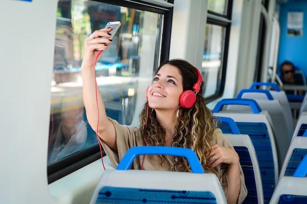 彼女の電話で電車の中でselfieを取っている若い女性。